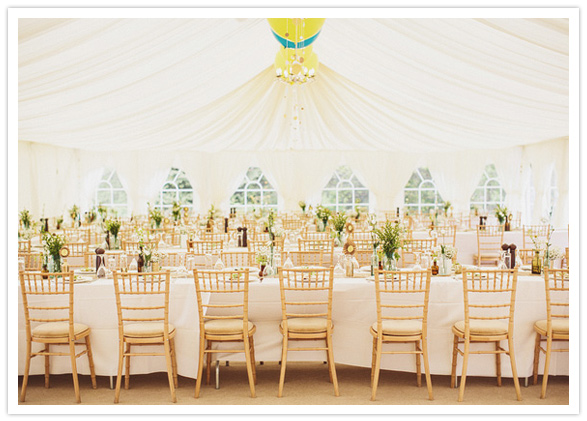 white tent and gold chairs wedding reception style